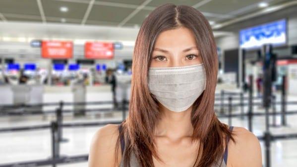 vrouw met mondkapje op vliegveld 600x337 1